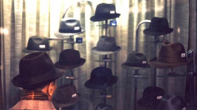 Un uomo di fronte una vetrina di cappelli